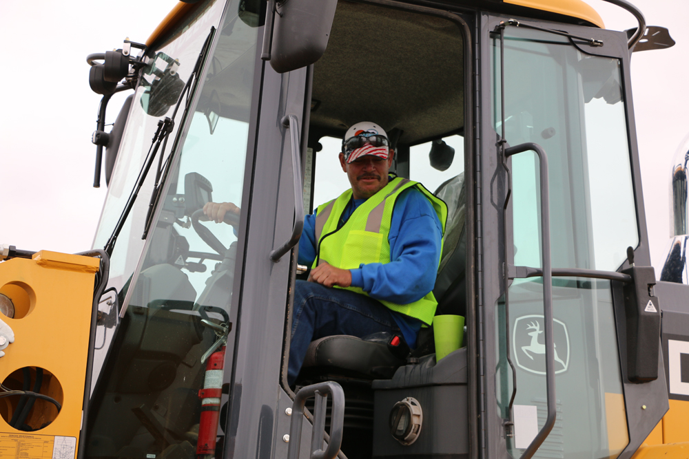 Public works employee driving tractor at clean up day