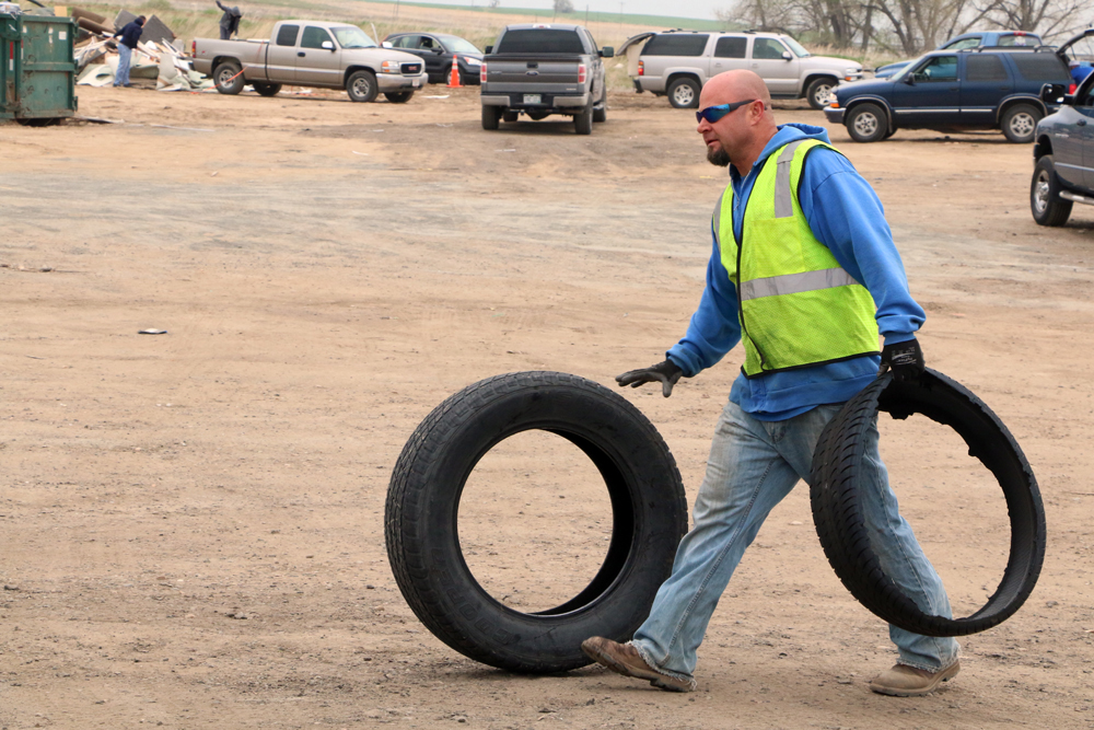 Public works worker rolling tires