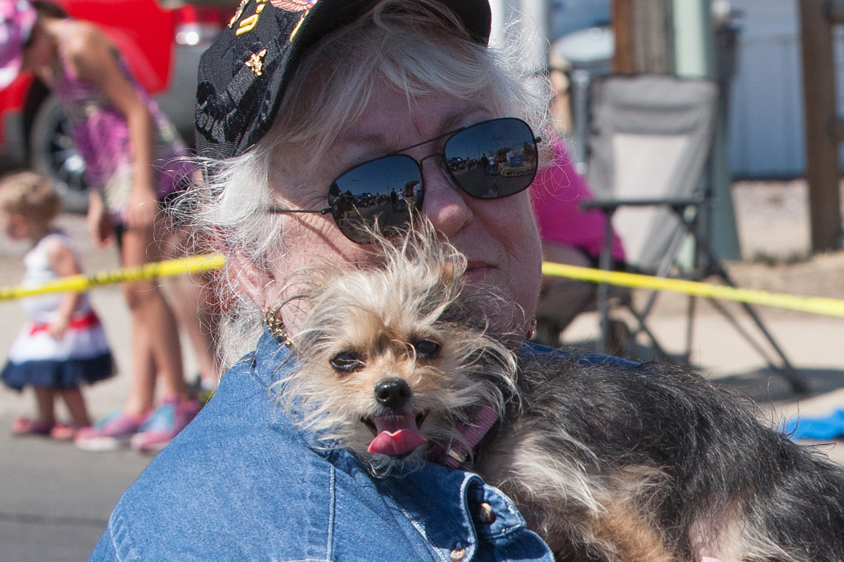 Woman with dog watching parade