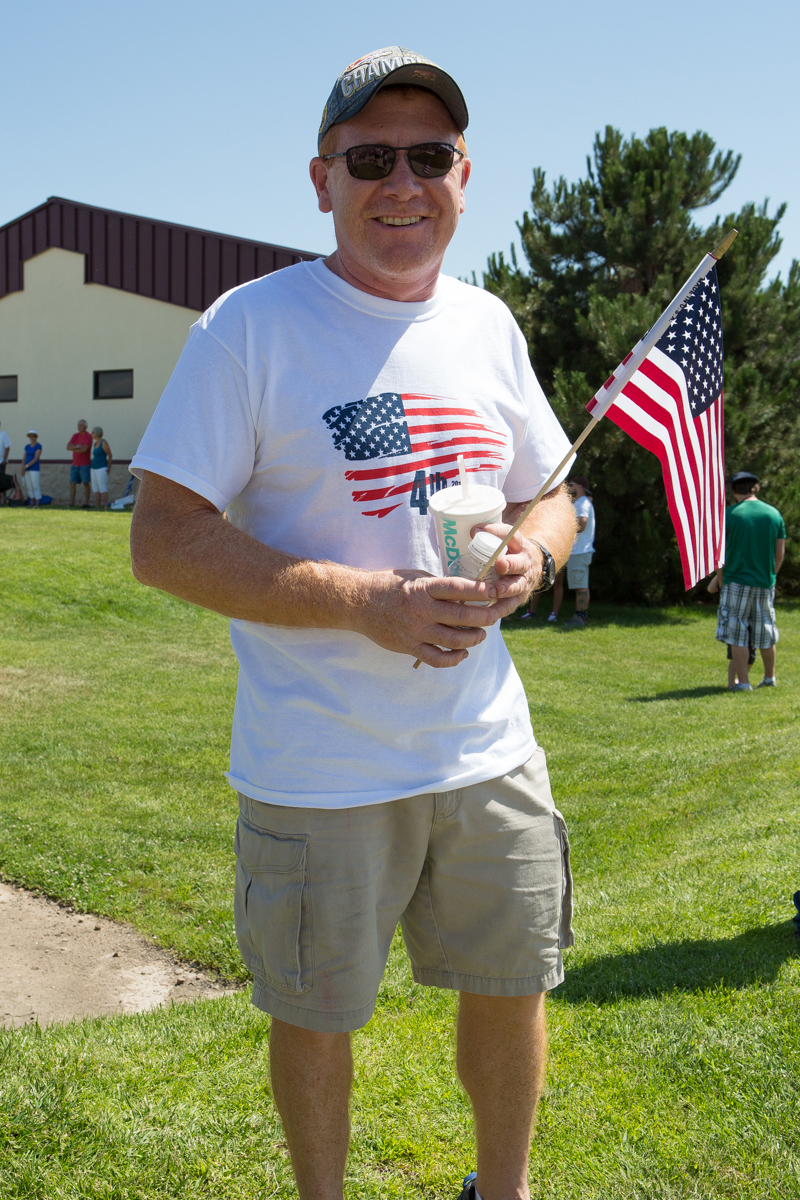 Man wearing American Flag T-shirt and holding an American Flag