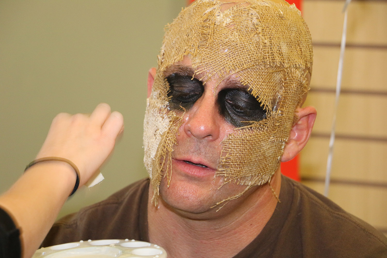 Makeup artist applying mask to mans face