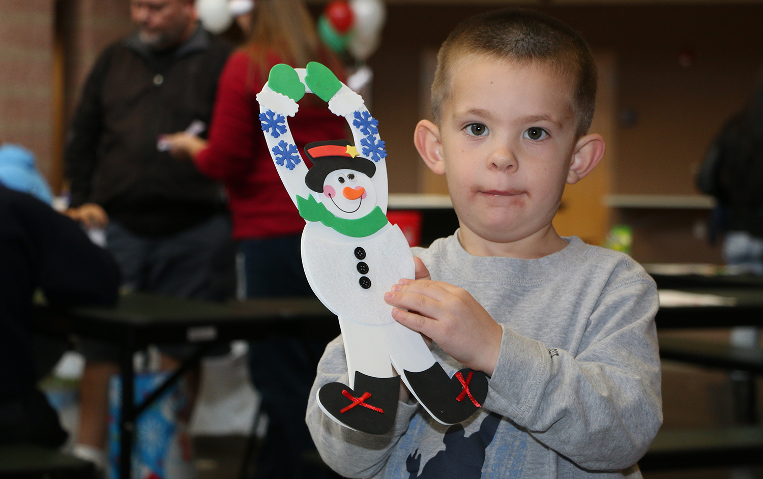 2016 Holiday Festival child holding up craft snowman